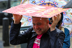 © Licensed to London News Pictures. 24/09/2019. London, UK. A protester shelter from the rain beneath a placard outside Supreme Court during heavy downpour in London. Photo credit: Dinendra Haria/LNP