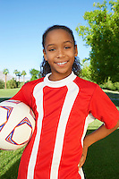 Girl (7-9 years) soccer player holding ball under arm, portrait