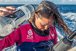 April 27, 2015. Leg 6 to Newport onboard Team SCA. Day 8. Sally Barkow rinses her face and hair with fresh water.