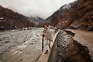 A Pakistani boy walks along a retaining wall next to a flood-damaged road, on 24 February, 2011, in Madyan, Swat Valley, Pakistan.