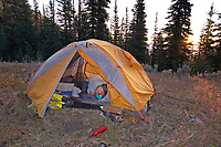 WA15249-00...WASHINGTON - Staying wrapped in a sleeping bag on a very chilly morning on Skull and Crossbones Ridge, the start of the final day of riding from Wenatchee to the Nighthawk Border Crossing.