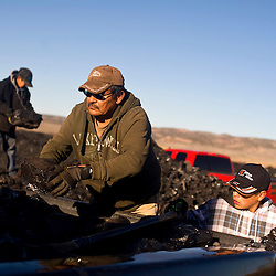 Lloyd Israel and his two grandsons Keanu and Garrick load coal at the public load out facility of the Kayenta Mine in Black Mesa, Ariz. The family uses coal to heat their home.