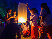 26 DECEMBER 2014 - PATONG, PHUKET, THAILAND: Thai students help tourists launch lanterns during memorial services for the victims of the 2004 tsunami on Patong Beach in Patong, Phuket. Hundreds of people died in Patong and nearly 5400 people died on Thailand's Andaman during the 2004 Indian Ocean Tsunami that was spawned by an undersea earthquake off the Indonesian coast on Dec 26, 2004. In Thailand, many of the dead were tourists from Europe. More than 250,000 people were killed throughout the region, from Thailand to Kenya. There are memorial services across the Thai Andaman coast this weekend.    PHOTO BY JACK KURTZ