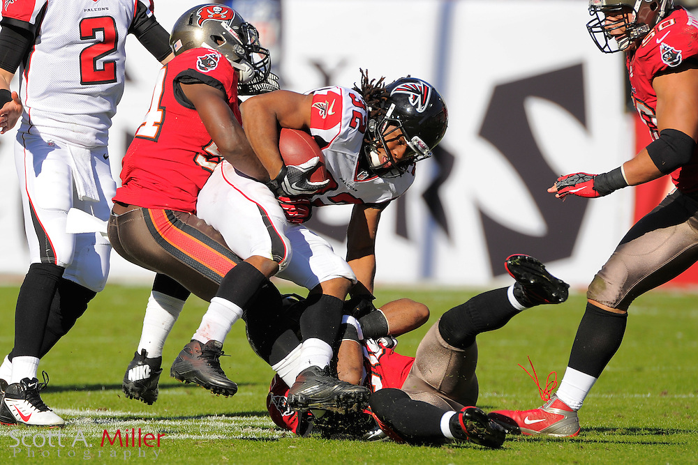 Atlanta Falcons running back Jacquizz Rodgers (32) is tackled by Tampa Bay Buccaneers outside linebacker Lavonte David (54) and free safety Ronde Barber (20) during the Falcons game against the Tampa Bay Buccaneers game at Raymond James on November 25, 2012 in Tampa, Florida.  Atlanta won 24-23...©2012 Scott A. Miller.
