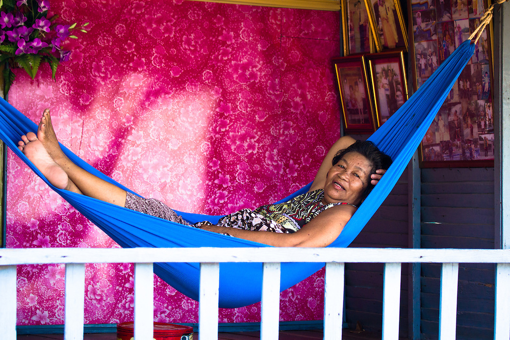 A woman relaxes in her hammock on the veranda of her floating house. In fact, the whole village she lives in, Chong Kos, floats on the Tonlé Sap River in Cambodia.