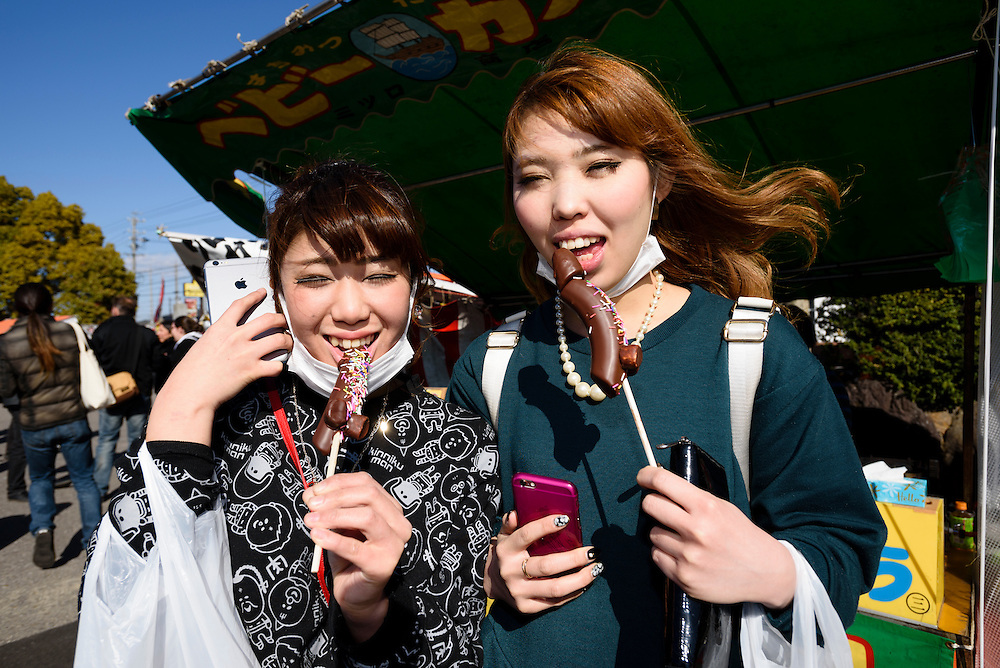 Women pose for a photograph while eating chocolate covered bananas shaped as phalluses during Honen-sai, a fertility festival at Tagata Shrine in Komaki, Aichi Prefecture, Japan. The traditional Shinto festival celebrates fertility and a bountiful harvest. The principal offering during the festival is a large wooden phallus. Each year a craftsman carves a new phallus from a Japanese cypress tree. It measures almost 2.4 meters (13 feet) long and weights 280kg (620 pounds).