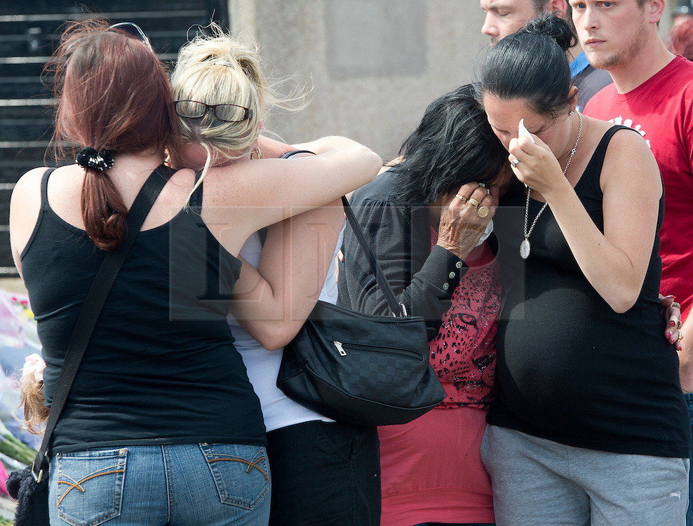 © Licensed to London News Pictures. 11/08/2012 . Grieving members of the public hugging next to flowers laid at the end of  The Lindens, New Addington where a body was discovered in the hunt for missing 12 year-old schoolgirl Tia Sharp. Photo credit : LNP