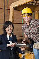 Portrait of female inspector and industrial worker using tablet PC