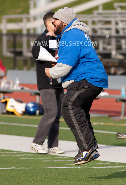 Newburgh, New York - A Middletown coach celebrates after a successful play during the Orange County Youth Football League Division II Super Bowl at Newburgh Free Academy on  Nov. 22, 2014.