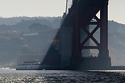 Public water ferry travels under the Golden Gate Bridge as seen from water level