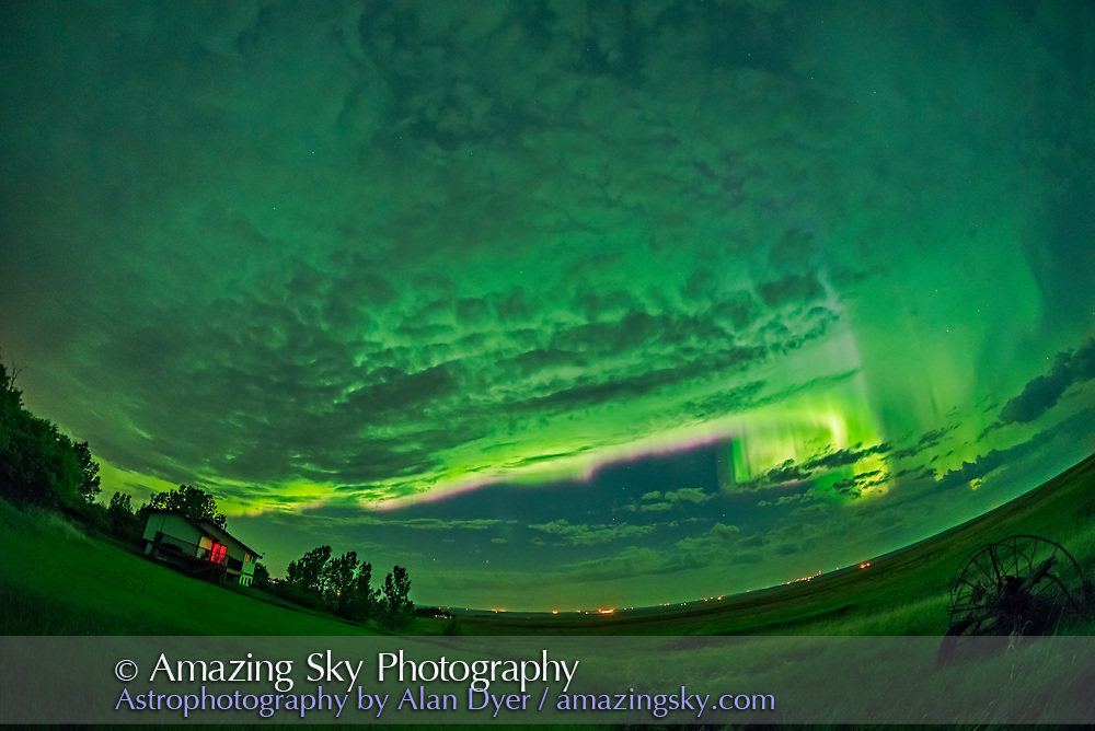 The great all-sky aurora of the night of May 27/28, 2017, shot from home in southern Alberta looking north toward the auroral oval. The curtain is fringed with pink from glowing nitrogen. The greens, here bright enough to light the ground, are from oxygen. <br /> <br /> This is a stack of 8 exposures for the ground to smooth noise, and one exposure for the sky, all 1.6-second exposures at f/2.8 with the 12mm Rokinon full-frame fish-eye lens and Nikon D750 at ISO 3200. Shot as part of a time-lapse sequence.