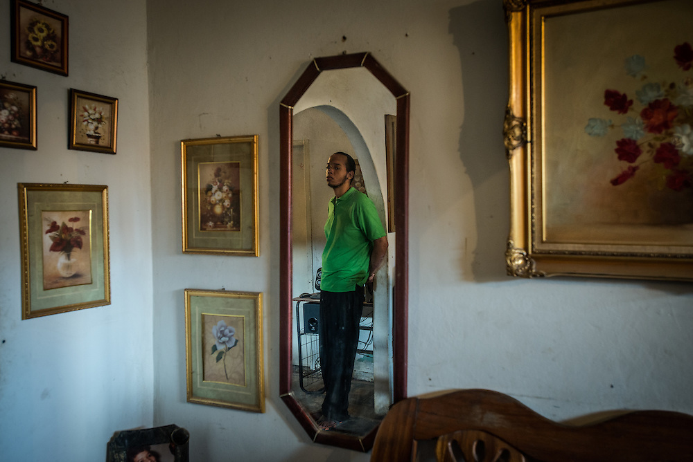 "MARACAY, VENEZUELA - JULY 4, 2016: Schizophrenic Gerardo Simeone stands in this spot in his family's living room for hours each day in silence, rarely even making eye contact with members of his family. Unlike his brother, Gerardo isn't prone to violence when his pills run out. He drifts into his own world, spending long spells standing calmly in a corner as the rest of his family sits in the living room watching television. He might look up and answer a question now and then, but it is like he is dreaming elsewhere.  ""We call him our Swiss Guard,"" jokes his father Mario.   PHOTO: Meridith Kohut for The New York Times"