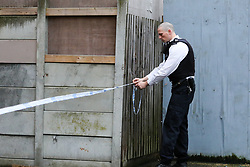 © Licensed to London News Pictures. 10/12/2019. London, UK.  A police officer puts crime scene tape around Shelley House, Boyton Road in Hornsey, after a man was fatally stabbed on Monday 9 December 2019.  Police were called to a residential address in Shelley House in north London following reports of a fight and a man having been stabbed. A man, aged in his 40s, was found suffering from a stab injury. He was pronounced dead at the scene. Two men aged 48 and 54 - have been arrested on suspicion of murder and are in police custody. Photo credit: Dinendra Haria/LNP