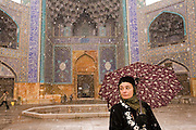 Isfahan, Iran. Faith D'Aluisio with an umbrella during a snowfall in front of the magnificently tiled Masjed-e Imam (Royal Mosque) in Imam Square, Isfahan, Iran. (Also referred to as Emam Square). Built by the Safavid ruler, Shah Abbas 1, as part of the renovation of the central square of Isfahan. The architect was Ostad Abu'l-Qasim.  (Imam Square is also called Naghsh-i Jahan Square).