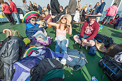 © Licensed to London News Pictures. 11/06/2015. East Cowes, UK.  Festival goers wearing mexican sombreros travelling to Isle of Wight Festival 2015 on the Southampton-East Cowes ferry early on thursday morning. surrounded by their bags and tents.This years festival include headline artists the Prodigy, Blur and Fleetwood Mac.  Photo credit : Richard Isaac/LNP