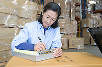 Woman making notes in distribution warehouse