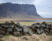 Rockwall at Núpsstaður, Southeast Iceland. Mount Lómagnúpur in background.
