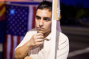 "Sept. 19 - PHOENIX, AZ: A protester who supports the DREAM Act stands in front of an American flag in Phoenix Sunday night. About 30 people met in front of US Sen. John McCain's office in Phoenix Sunday night to demonstrate in support of the DREAM Act, which is scheduled to be debated in the US Senate on Tuesday, Sept 21. The Development, Relief and Education for Alien Minors Act (The ""DREAM Act"") is a piece of proposed federal legislation in the United States that was introduced in the United States Senate, and the United States House of Representatives on March 26, 2009. This bill would provide certain illegal immigrant students who graduate from US high schools, who are of good moral character, arrived in the U.S. as minors, and have been in the country continuously for at least five years prior to the bill's enactment, the opportunity to earn conditional permanent residency. In the early part of this decade McCain supported legislation similar to the DREAM Act, but his position on immigration has hardened in the last two years and he no longer supports it. The protesters, mostly area students, marched and drilled to show their support for the US military and then held a candle light vigil.   Photo by Jack Kurtz"
