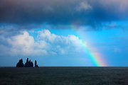A rainbow starts to rise from the Atlantic Ocean not far from Reynisdrangar sea stacks just off Reynisfjara beach near Vík í Mýrdal, Iceland. There are a number of Iceland legends about the basalt sea stacks. In the most common legend, two trolls were turned to stone as they were caught dragging a three-masted ship to shore at daybreak.