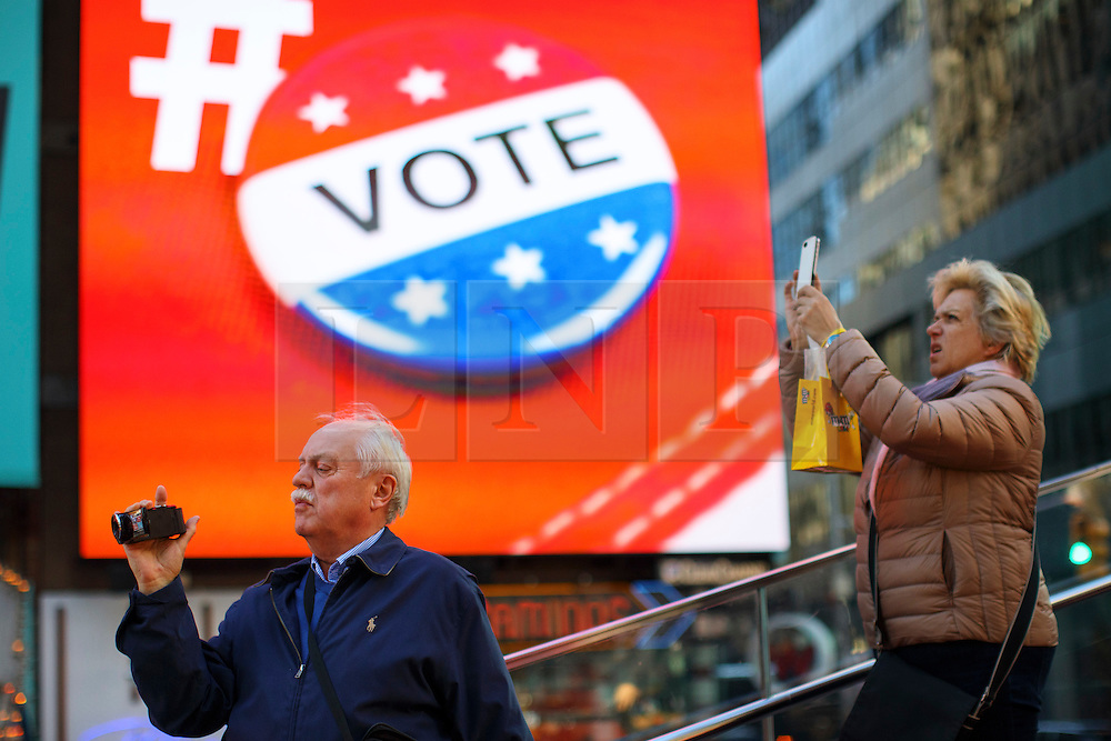 © Licensed to London News Pictures. 07/11/2016. New York CIty, USA. Tourists take pictures next a voting reminder advertisement screen in Times Square, New York City on Monday, 7 November, the day before the presidential election day in the United States of America. Photo credit: Tolga Akmen/LNP