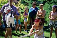 Girl, 8-10, hits pinata at outdoor party