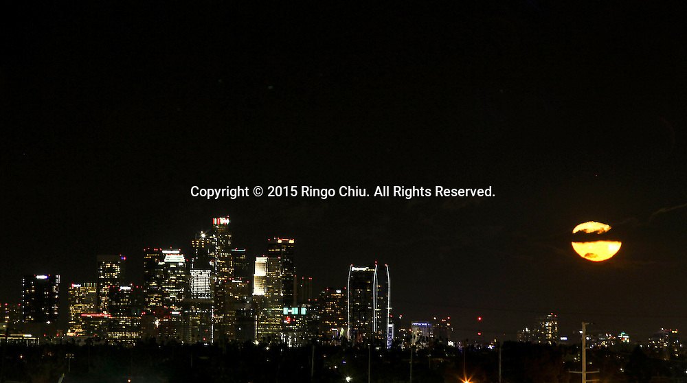 The moon rises behind the downtown Los Angeles skyline on Monday, December 28, 2015.