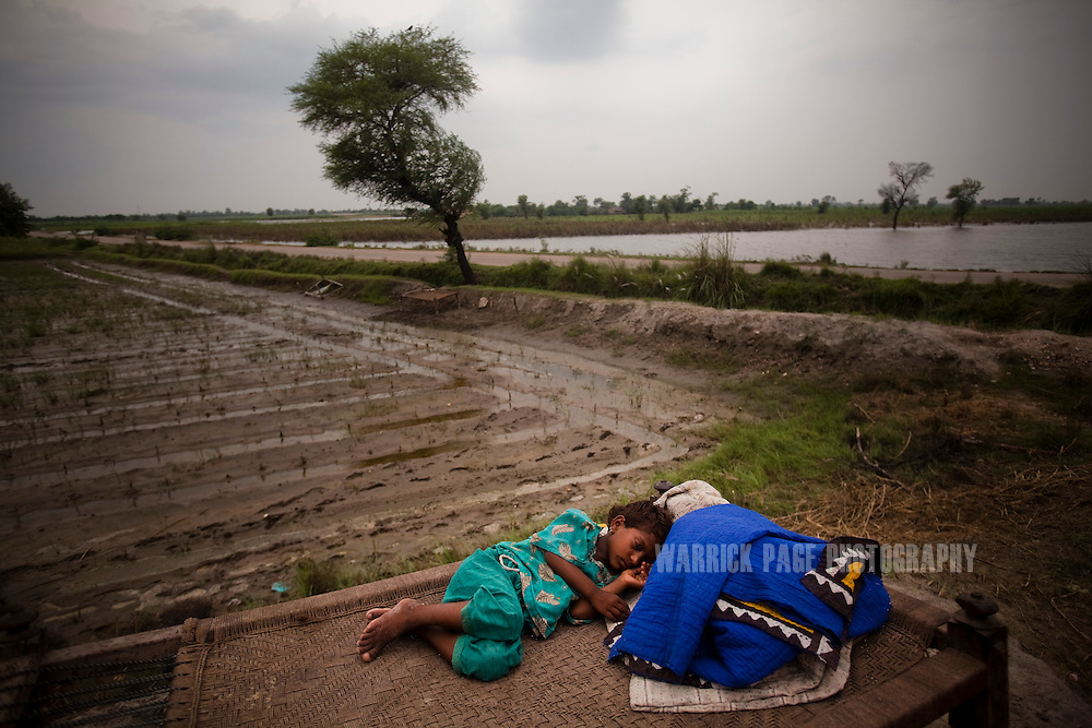 A young girl displaced by rising floodwaters, sleeps on a charpoi in the open, on 12 September, 2011, in Benazirabad, Pakistan. More than 17% of children in the flood areas are severely acutely malnourished and 67% of livestock has been destroyed after torrential monsoon rains, reminiscent of the 2010 floods that devastated Pakistan, have reportedly already killed over 200 people, left 300,000 homeless and affected over 7 million. (Photo by Warrick Page)