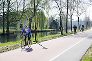 In Nieuwegein genieteen wielrenner langs het Merwedekanaal van het mooie lenteweer.<br /> <br /> In Nieuwegein a cyclist on a road bike is enjoying the nice weather in the spring.