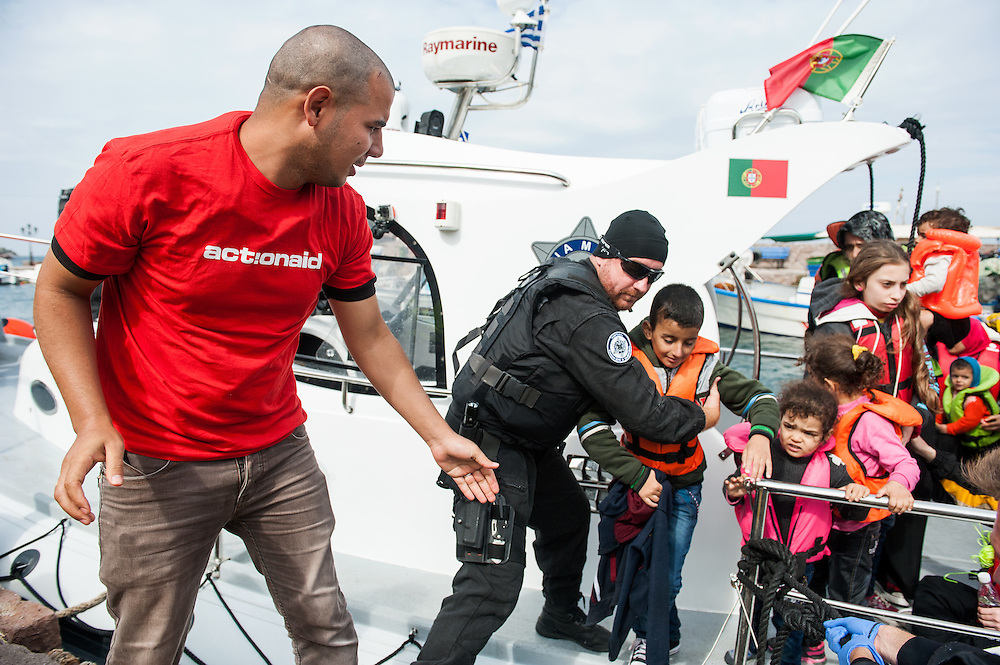 Moustafa, Arabic translator of ActionAid Hellas, helps a child to get off the Portuguese coast guard boat at  the fishing harbour of Skala Sykamias, Lesvos, Greece.