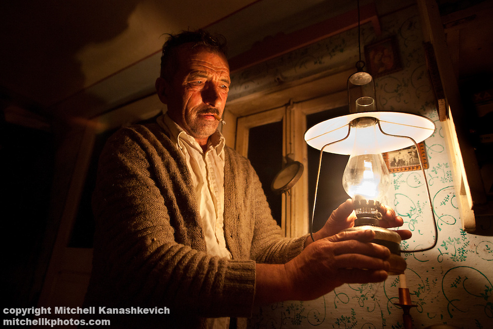 Rural Romanian man lighting a kerosene lamp in the remote village of Holbav, which as odf 2010 does not have running water or electricity