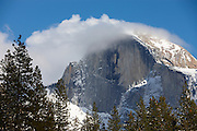 A winter snow storm passes over Half Dome, a granite peak that rises more than 4,737 ft (1,444 m) above the valley floor of Yosemite National Park, California.