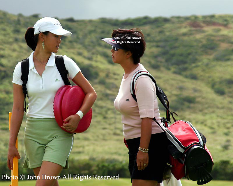 Fifteen year old Michelle Wie has a conversation with her mother Bo while walking to the practice range with training aids prior to the 2005 SBS LPGA Women's Open at Turtle Bay Resort in Kahuku, Hawaii.