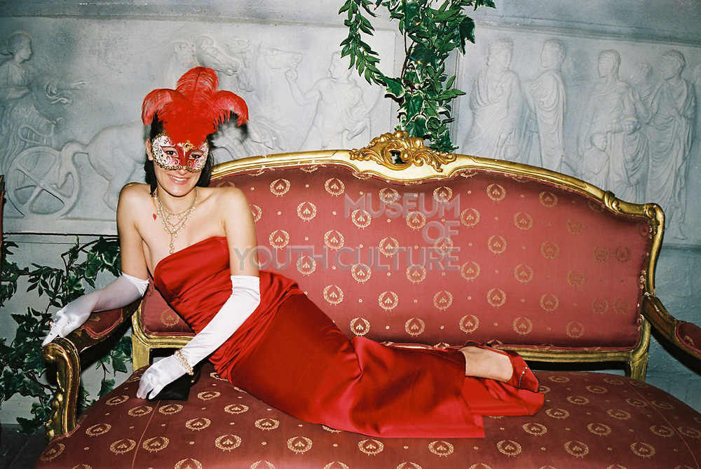 Woman wearing red satin cocktail dress, feathered masquerade mask, long evening gloves reclining on a sofa, Posh at Addington Palace, UK, August, 2004
