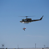 A UH-1 hey lifts a Para-Rescueman with a simulated patient up to safety during a Special Operation demonstration. Help from the ground in two forms - a guide/stabilization rope and defense to ensure a successful mission.