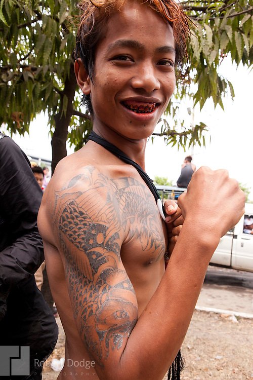andalay, Myanmar- April 14, 2013: This young man shows off his tattoos during Myanmar's Thingyan Water Festival. Thingyan is held in April, one of the hottest months of the year in Myanmar. The water festival marks the country's New Year celebration and the festival includes lots of drinking, singing, dancing and theater. Wherever you are you are likely to get doused with water as the Burmese see this as a cleansing of the previous year's sins and bad luck and a blessing for good luck and prosperity in the year ahead. In the major cities of Mandalay and Yangon, large platforms are erected along major roadways and are equipped with high powered water hoses. The platforms, sponsored by large corporate donors, also have dance stages and play the latest pop and hip hop music. Thousands of residents pour into the streets by foot, motorbike and flatbed truck to get hosed under the platforms while they drink and dance. Many of the young celebrants wear their best clubbing clothes. And many of the party goers are men, having left their wives and girlfriends at home.