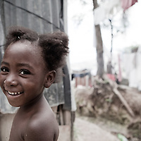 A young girl smiles in a tented camp in Port au Prince, Haiti