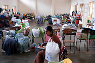 A woman whose home was destroyed by the December 26, 2004 Tsunami which struck S.E. Asia following a 9.0 earthquake in the Indian Ocean eats a meal provided by relief operations in one of the buildings of the Batticaloa Hindu College where she now lives. Batticaloa, Sri Lanka. 11/01/2005. Photo © J.B. Russell