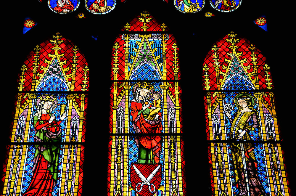 Freiburg Minster Stained Glass Window in Freiburg im Breisgau, Germany <br /> When the Freiburg Minster cathedral was built mostly in the 13th century, the local guilds donated the funds for the stained glass windows but insisted that their symbols be incorporated into these colorful works of art.  For example, if you look closely below the image of the Madonna with Child, you will see a scissors representing the tailors&rsquo; guild.  On the left is Mary Magdalene and on the right is St. Catherine of Alexandria.