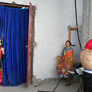 Yolanda La Amorosa (centre) warms up in the dressing room for her bout while male wrestlers prepare during the 'Titans of the Ring' wrestling group's Sunday performance at El Alto's Multifunctional Centre. Bolivia. The wrestling group includes the fighting Cholitas, a group of Indigenous Female Lucha Libra wrestlers who fight the men as well as each other for just a few dollars appearance money. El Alto, Bolivia, 14th March 2010. Photo Tim Clayton
