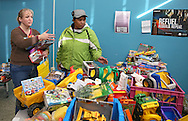 Volunteer Tracie Lawrance (from left) helps Annie Hughes, both of Cedar Rapids, pick out Christmas gifts for her 6 children during the HD Center Christmas party at Metro High School, 1212 7th St. SE in Cedar Rapids on Saturday, December 22, 2012.
