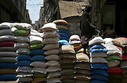 A Pukhtun laborer waits to load bags full of rice and wheat at a wholesale market in Karachi, Pakistan.