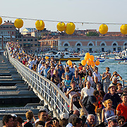 VENICE, ITALY - JULY 20: Pilgrims walk on the votive bridge while people gather on boats of all sizes in St Mark's basin for the Redentore Celebrations on July 20, 2013 in Venice, Italy. Redentore is one of the most loved celebrations by Venetians which is in remembrance for the end of the 1577 plague. Highlights of the celebration include the pontoon bridge extending across the Giudecca Canal, gatherings on boats in the St Mark's basin and a spectacular fireworks display. (Photo by Marco Secchi/Getty Images)