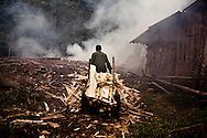 A worker brings scrap wood to burn at a wood and paper factory along the Red River near Yen Bai Province in northern Vietnam, Asia.