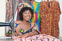 Beautiful African American female tailor looking away while stitching cloth on sewing machine