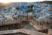 A teenage boy gives scale to Fatehpol Gate, one of 7, to Mehrangarh Fort, with the blue houses of the district of Navchokya beyond.