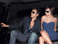 Young couple in backseat of limousine wearing evening dress and sunglasses