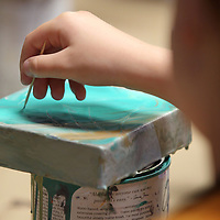"""Allie Grisham, 7, of Blue Springs, uses a toothpick to expose the bottom layer of paint as she works on her """"Chalk Paint Pour"""" project at their Art/DIY Camp at Farmhouse in Tupelo on Tuesday morning."""