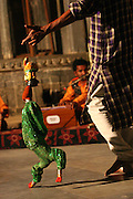 A Rajasthani man performs traditional puppetry, a comical presentation where the puppet can be flipped and its head detached at the cues of unique whistles of the puppeteer; Udaipur, the lake city of Rajasthan, India. .Photo by Suzanne Lee