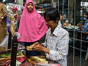 06 JULY 2016 - BANGKOK, THAILAND: A Muslim girl buys candy from a street vendor in front of Ton Son Mosque in the Thonburi section of Bangkok before Eid services at the mosque. Eid al-Fitr is also called Feast of Breaking the Fast, the Sugar Feast, Bayram (Bajram), the Sweet Festival or Hari Raya Puasa and the Lesser Eid. It is an important Muslim religious holiday that marks the end of Ramadan, the Islamic holy month of fasting. Muslims are not allowed to fast on Eid. The holiday celebrates the conclusion of the 29 or 30 days of dawn-to-sunset fasting Muslims do during the month of Ramadan. Islam is the second largest religion in Thailand. Government sources say about 5% of Thais are Muslim, many in the Muslim community say the number is closer to 10%.        PHOTO BY JACK KURTZ