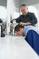 Barber washing mans head in barber shop
